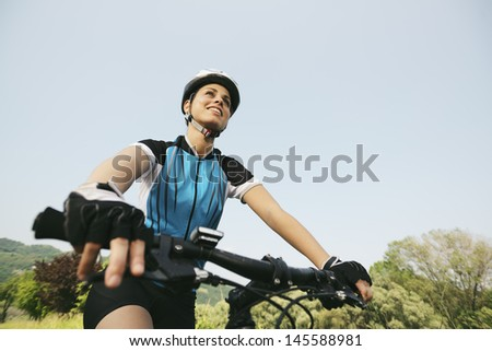 young woman training on mountain bike and cycling in park. Copy space, low angle view - stock photo