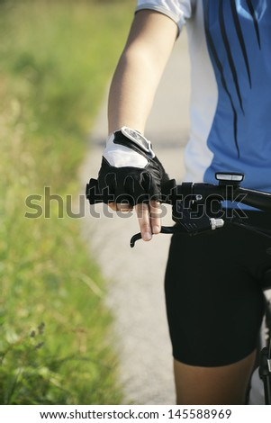 young woman training on mountain bike and cycling in park. Cropped view - stock photo