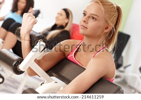 Young woman training on weight machine at the gym.