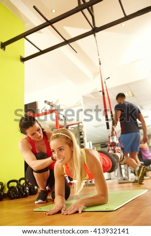 Young woman training with coach in fitness club. - stock photo