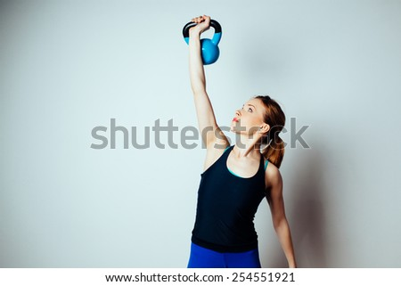Young woman training with kettlebell - stock photo