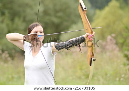 Young woman training with the bow  - stock photo