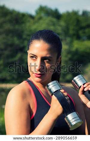 Young Woman Training with Weight in Nature
