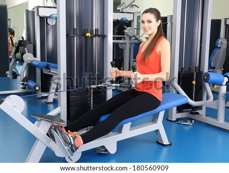 Young woman training with weights in gym  - stock photo