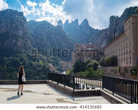 Young woman traveler enjoying the view of mountains on the background. Montserrat. Spain. Europe.