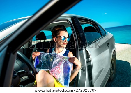 Young woman traveler sitting with paper map in the car and looking where to go on blue sea background