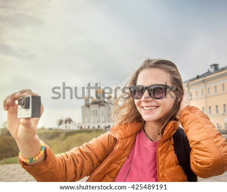 Young woman traveler with a camera in hand. Against the background of an orthodox temple. Travel to Russia - stock photo