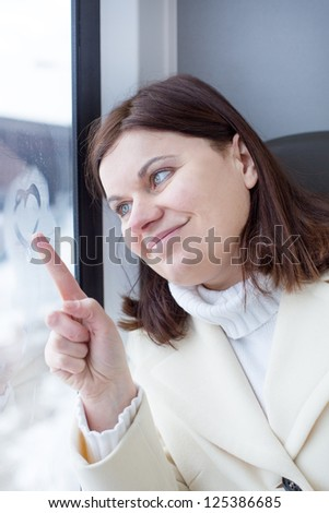 Young woman traveling by train and drawing heart on the window, while it moving. travel - stock photo