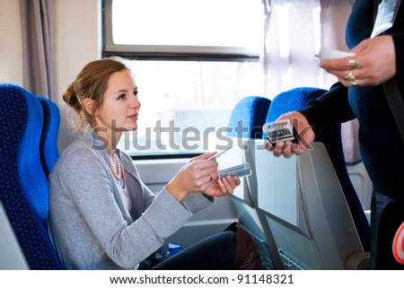 Young woman traveling by train, having her ticket checked by the train conductor - stock photo