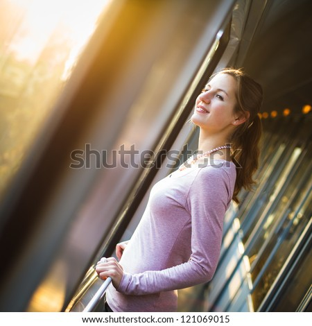 Young woman traveling by train, watching the passing country side while standing in the train corridor - stock photo
