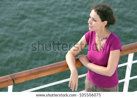 young woman traveling on ship looks into distance - stock photo