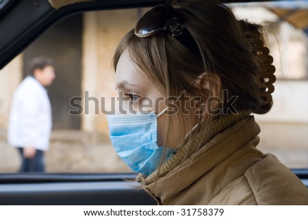 Young woman travels on automobile in a protective mask - stock photo