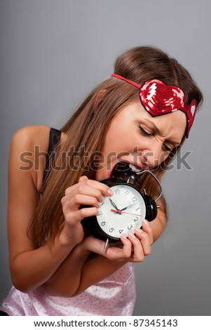 Young woman tries to eat the clock - stock photo