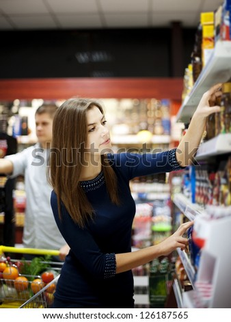 Young woman trying make a choice in supermarket - stock photo
