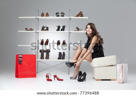 young woman trying on black high heels - stock photo