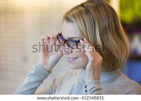 Young woman trying on glasses - stock photo