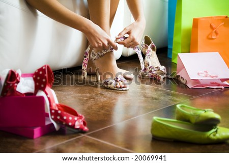 Young woman trying on high heel shoes - stock photo
