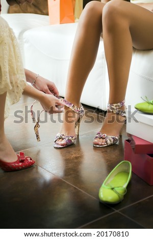 Young woman trying on high heel shoes, woman tying straps of shoes - stock photo