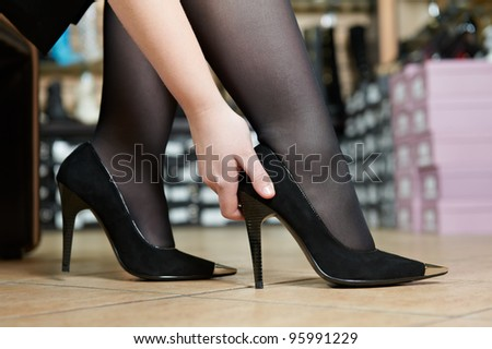Young woman trying on new shoes during footwear shopping at shoe shop - stock photo