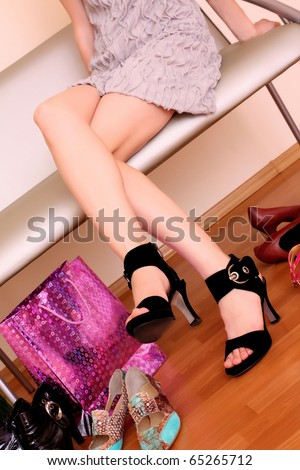 Young woman trying on new shoes in a store. - stock photo