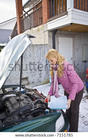 Young woman trying to fix the car - stock photo
