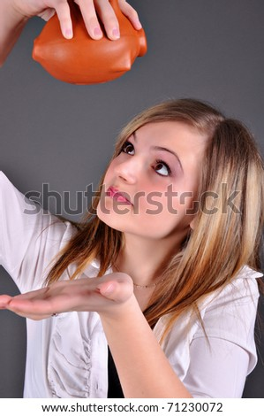 Young woman trying to get money from her piggy bank, isolated on grey background