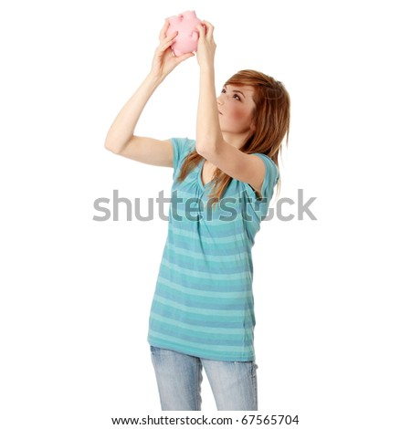Young woman trying to get money from her piggy bank, isolated on white background - stock photo