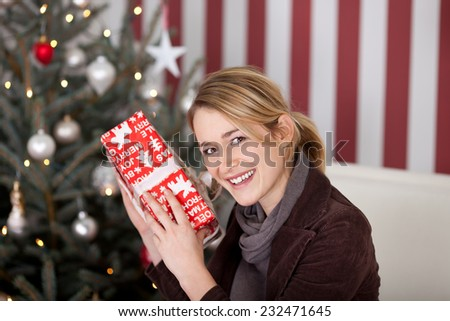 Young woman trying to guess the contents of a Christmas gift holding it to her ear as she shakes it and smiles at the camera - stock photo