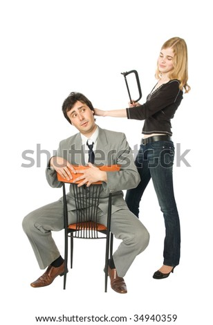 Young woman trying to saw off man's head - stock photo