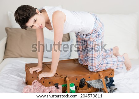 Young woman trying to squash luggage into a suitcase kneeling on top of the lid with a frown as she realises it will not possibly close - stock photo