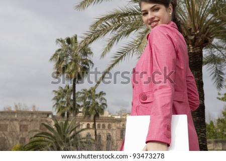 Young woman turning around while walking and holding a laptop computer under her arm. - stock photo
