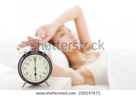 young Woman turning off the alarm clock on the bed - stock photo