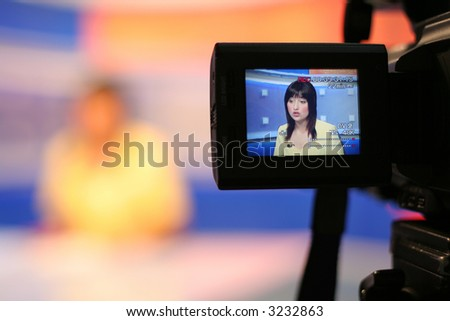 Young woman TV reporter presenting the news, view in video camera display - stock photo