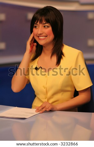 Young woman TV reporter smiling and listening in earphone while preparing for the news presenting - stock photo