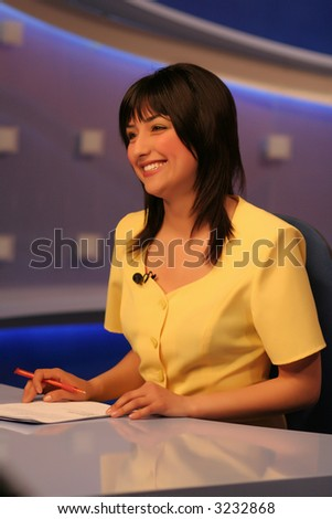 Young woman TV reporter, smiling and presenting the news - stock photo