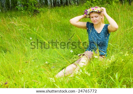 Young woman twining a  wreath on the meadow - stock photo
