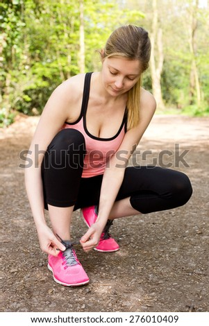 young woman tying her laces while out running - stock photo