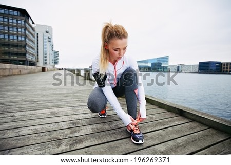 Young woman tying her shoelaces before a run along waterfront. Female runner preparing foe sprint. Fit female athlete on boardwalk along river. - stock photo