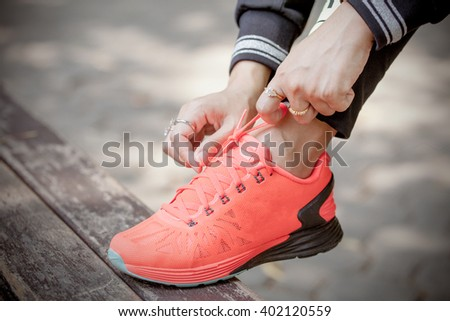 Young woman tying her shoes, prepared for jogging