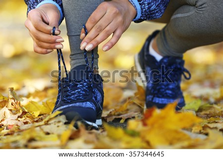 Young woman tying laces on her sport shoes before training in autumn forest.