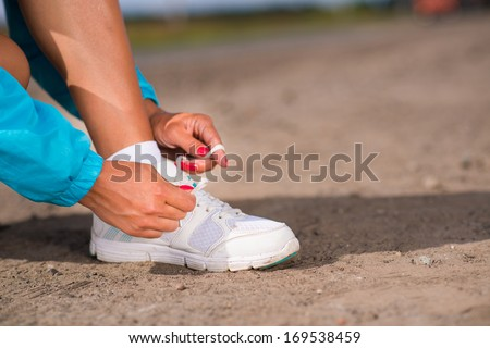 young woman tying shoelaces on sneakers on a rural road, exercise outdoors - stock photo