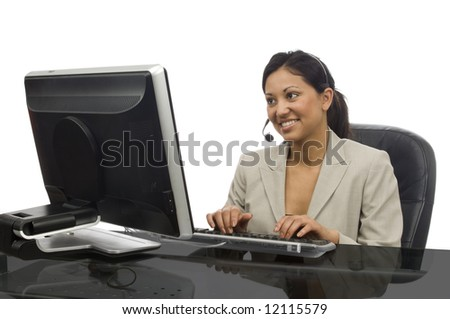 Young woman typing at a monitor with a telephone headset