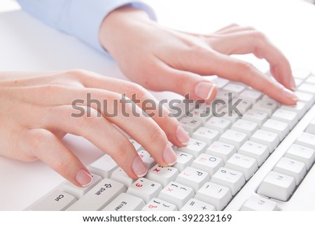 young woman typing on a keyboard - stock photo