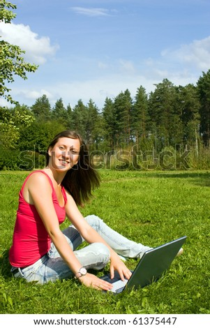 Young woman typing on a laptop outside on the grass