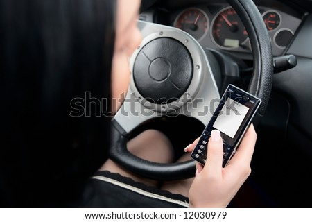 Young woman typing text message while driving - stock photo