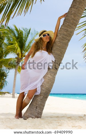 Young woman under a palm on the Maldivian beach - stock photo