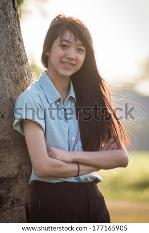 young woman under a tree in summer - stock photo