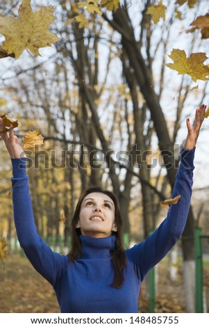 Young woman under falling leaves in the park - stock photo