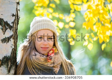 Young woman under tree in park in autumn