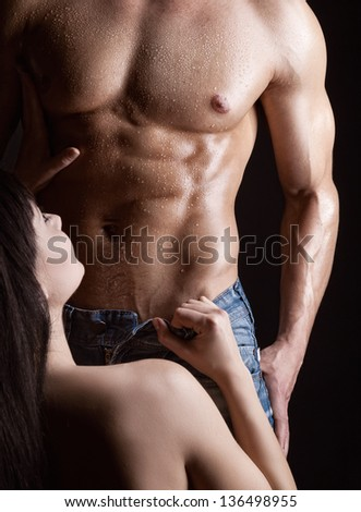 Young woman undressing muscular man on dark background - stock photo